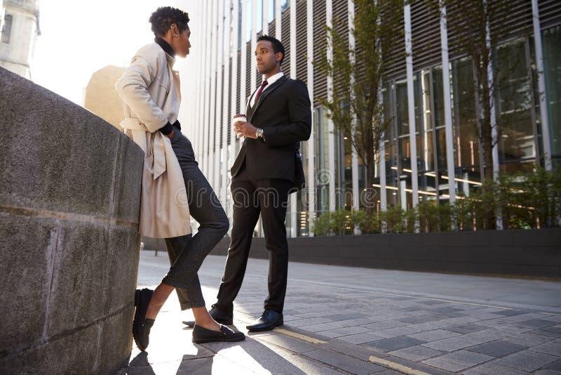 Zwei junge erwachsene Kollegen, die auf der sprechenden Straße, niedriger Winkel stehen lizenzfreie stockfotografie