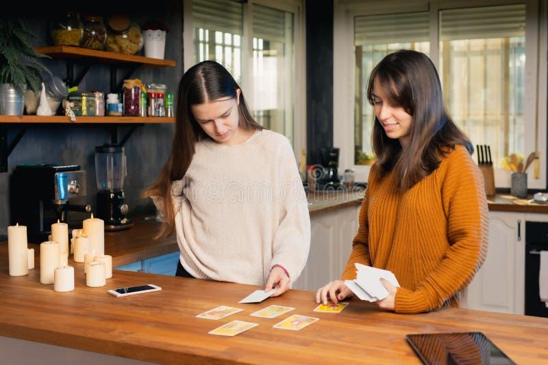 Zwei junge Feministinnen, die sich in einer Küche mit Kerzen über die Tarotkarten setzen lizenzfreie stockbilder