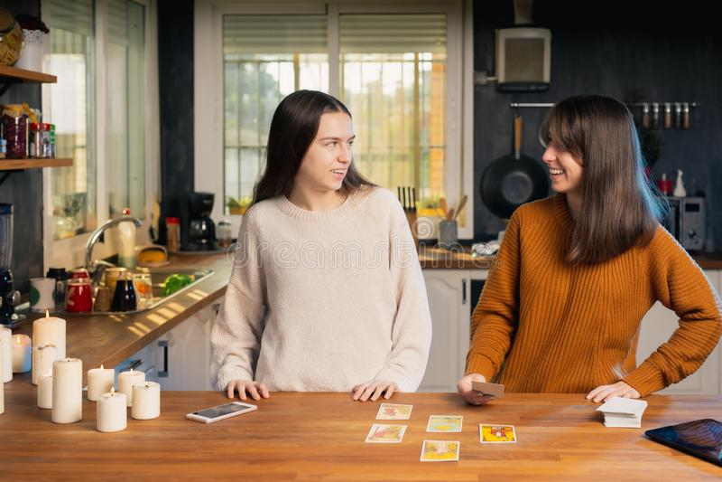 Zwei junge Feministinnen lachen über eine Karte, die in einer Küche in einem Tarot-Spiel gezeichnet wurde lizenzfreie stockfotografie