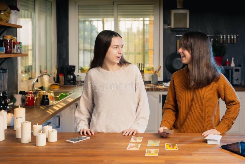 Zwei junge Feministinnen lachen über eine Karte, die in einer Küche in einem Tarot-Spiel gezeichnet wurde stockfotografie