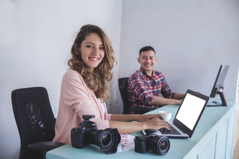 Zwei junge Fotografen, die an ihrem Laptop und Computer arbeiten lizenzfreie stockfotografie