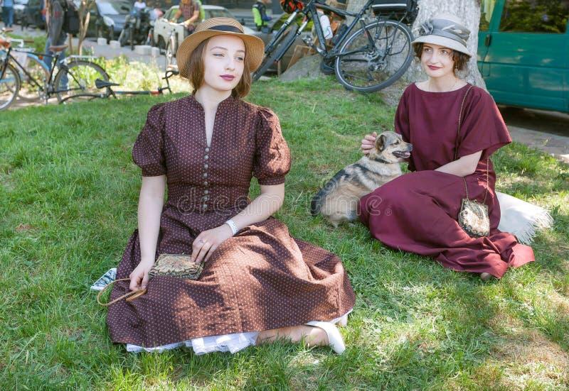Zwei junge Frauen auf alte Mode kleidet das Sitzen auf dem Boden und die Aufstellung mit kleinem Hund stockfoto