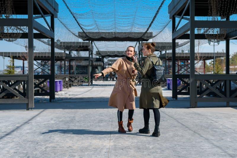 Zwei junge Frauen beschichtet im Frühjahr und Rucksäcke gehen auf der Rückseite des Stadt Parks lizenzfreies stockfoto