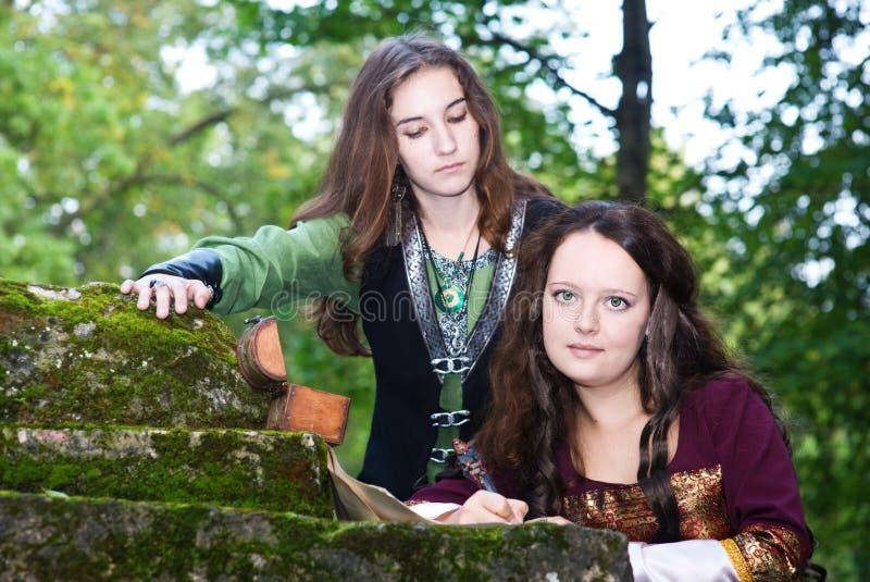 Zwei junge Frauen in den mittelalterlichen Kleidschreibenspapieren lizenzfreie stockbilder