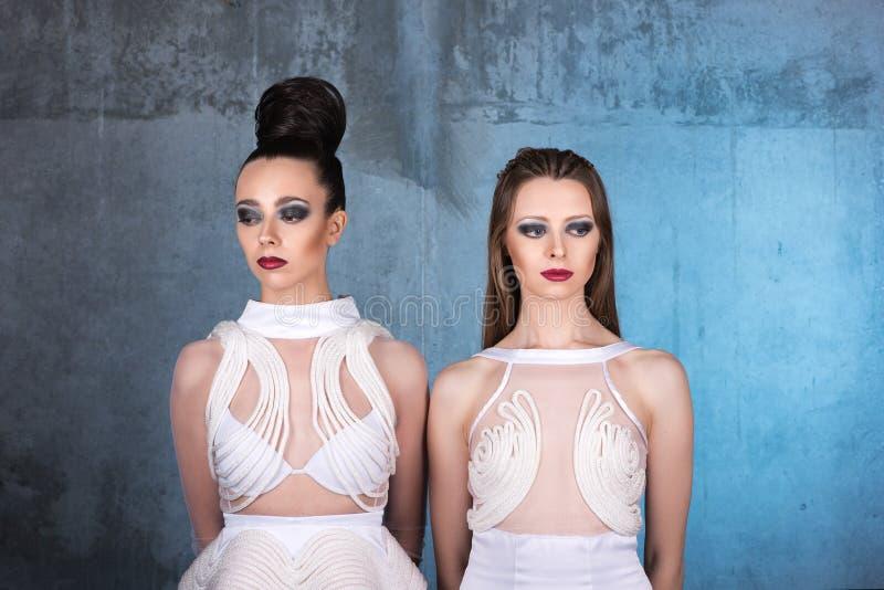 Zwei junge Frauen in den weißen Kleidern schauen in den verschiedenen Richtungen lizenzfreie stockfotografie