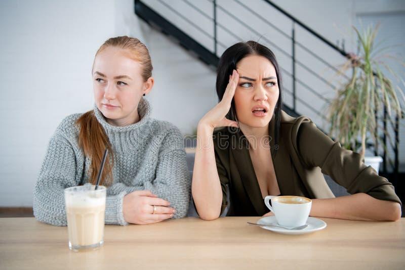 Zwei junge Frauen der Mädchen, die in einem Café mit den Kaffeetassen, entgegengesetzte Richtung schauend sitzen lizenzfreies stockfoto