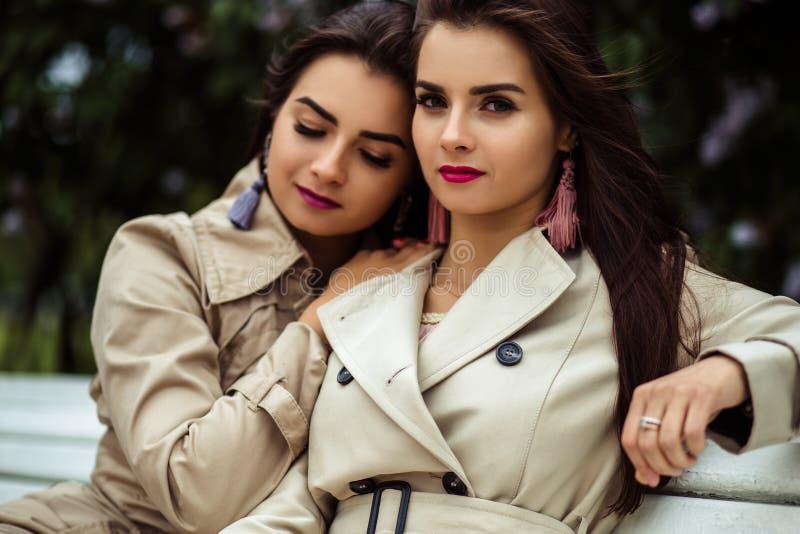 Zwei junge Frauen der schönen Zwillinge in der nahen blühenden Flieder der Regenmäntel lizenzfreie stockfotografie