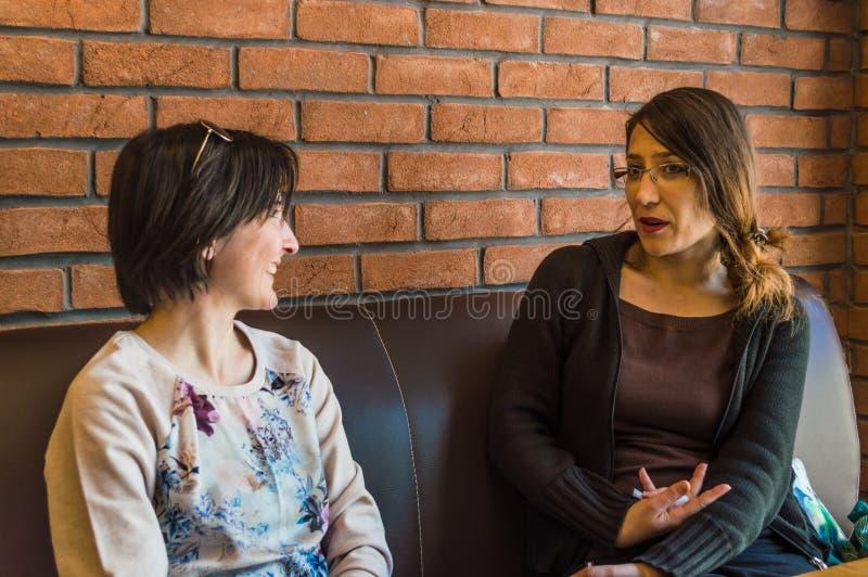 Zwei junge Frauen des Brunette, die in einem Café hat Gespräch sitzen lizenzfreies stockbild