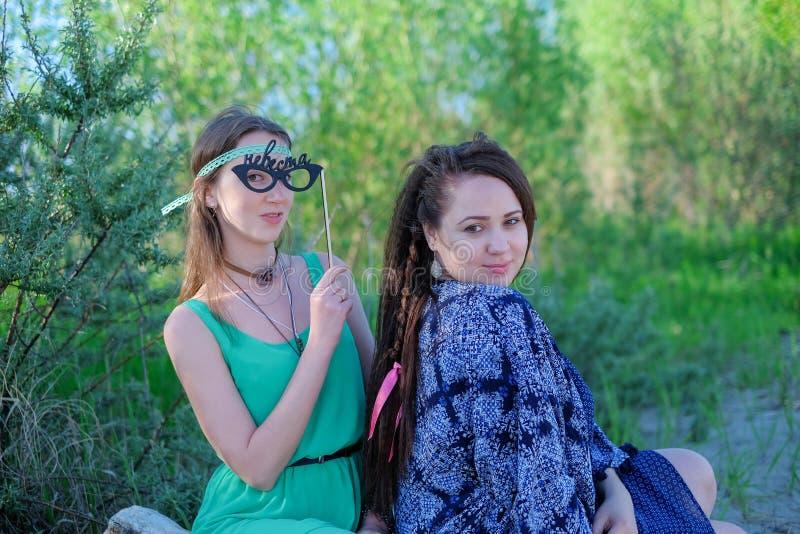 Zwei junge Frauen, die auf dem Gras hat gute Zeit sitzen lizenzfreies stockbild