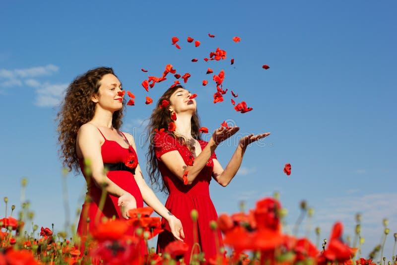 Zwei junge Frauen, die auf dem Mohnblumengebiet spielen lizenzfreie stockfotos