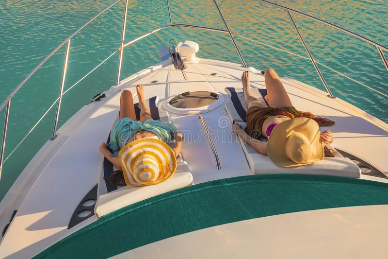 Zwei junge Frauen, die das Faulenzen auf Yacht unter der Sonne stillstehen stockfotos