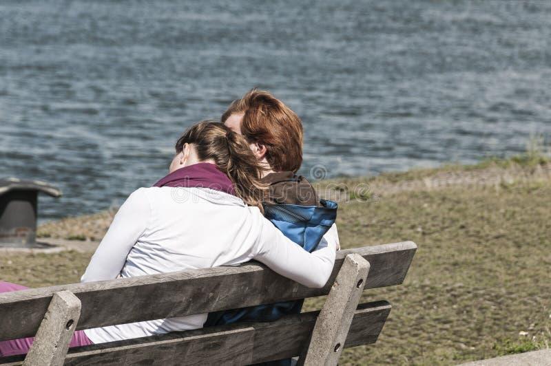 Zwei junge Frauen, die draußen auf einer Bank sitzen lizenzfreies stockbild