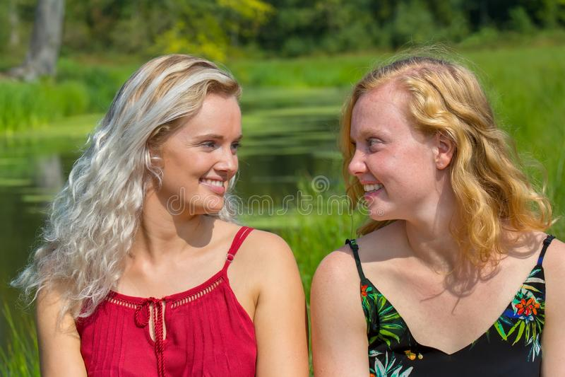 Zwei junge Frauen, die an einander lächeln stockfotos