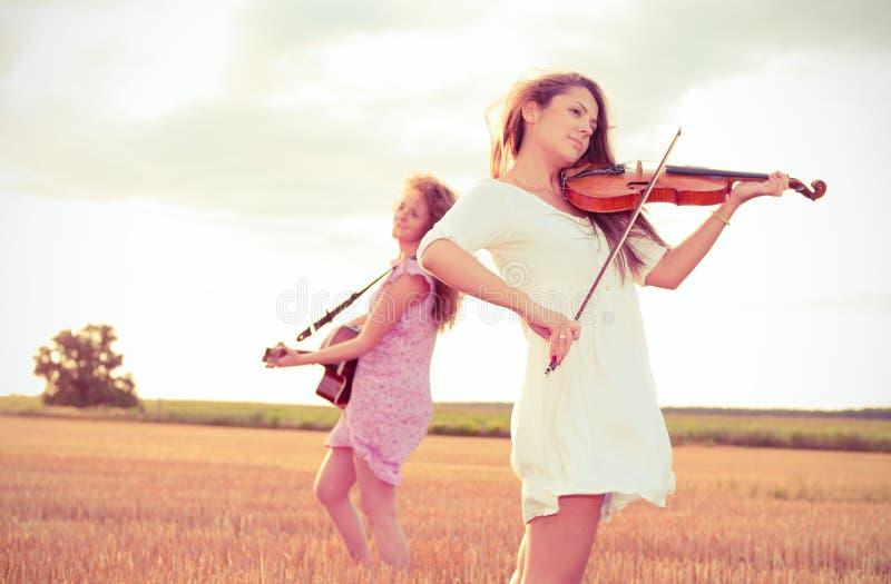 Zwei junge Frauen, die Gitarre spielen lizenzfreie stockfotos