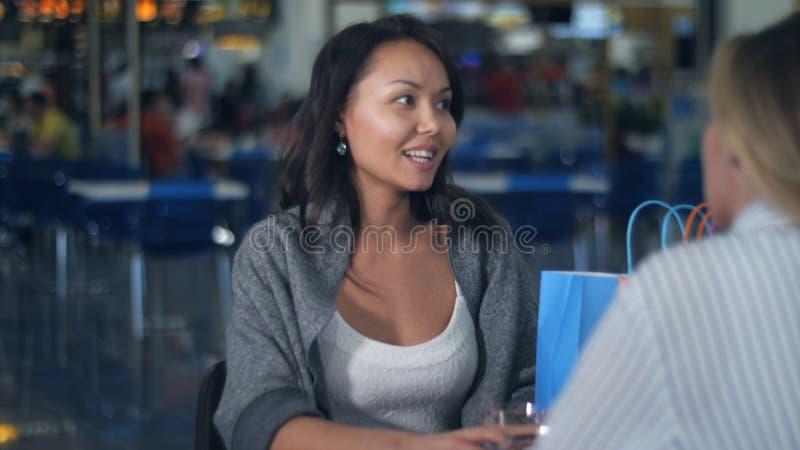 Zwei junge Frauen, die Kaffeepause nach dem Einkauf im Mall haben stockfotos