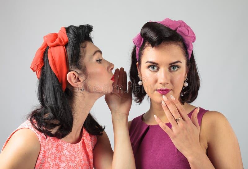 Zwei junge Frauen, die Klatsch flüstern stockbild