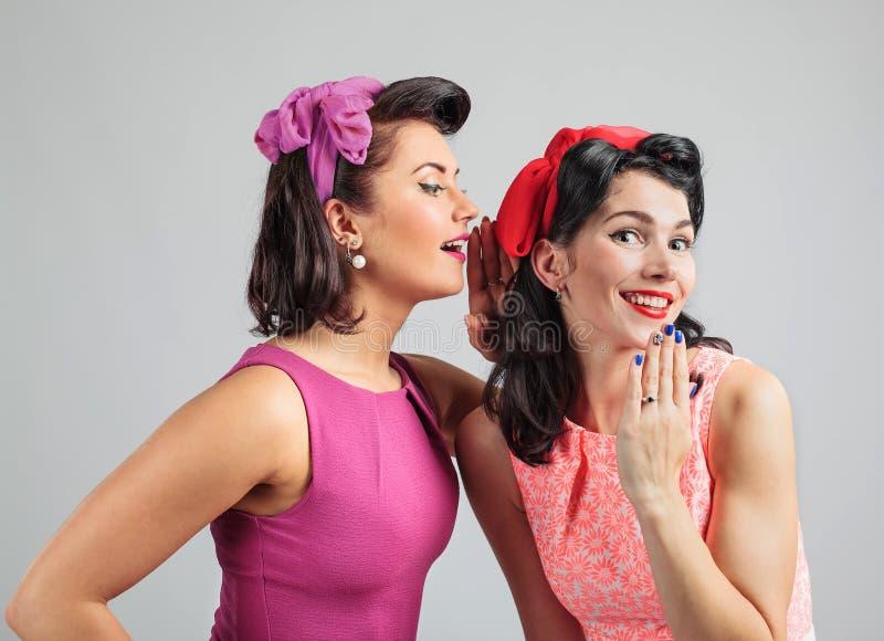 Zwei junge Frauen, die Klatsch flüstern stockfotos