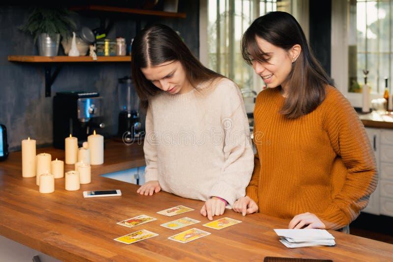 Zwei junge Frauen, die sich Sorgen über die Bedeutung von Tarotkarten machen, die in einer Küche gespielt werden lizenzfreie stockbilder