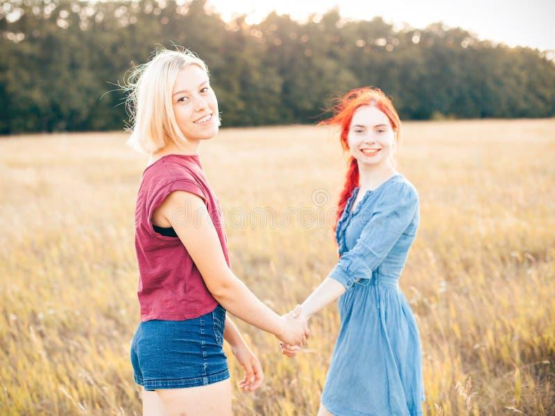 Zwei junge Frauen, die Spaß auf dem Feld haben lizenzfreie stockbilder