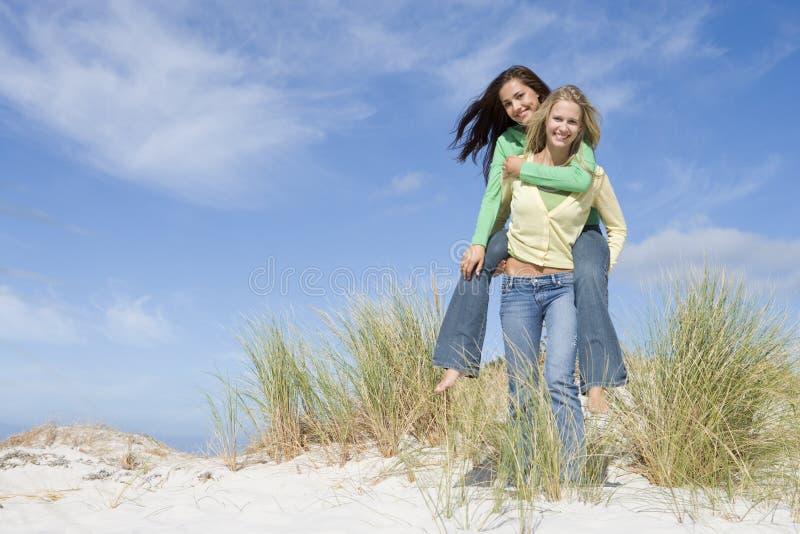 Zwei junge Frauen, die Spaß in den Dünen haben stockbilder
