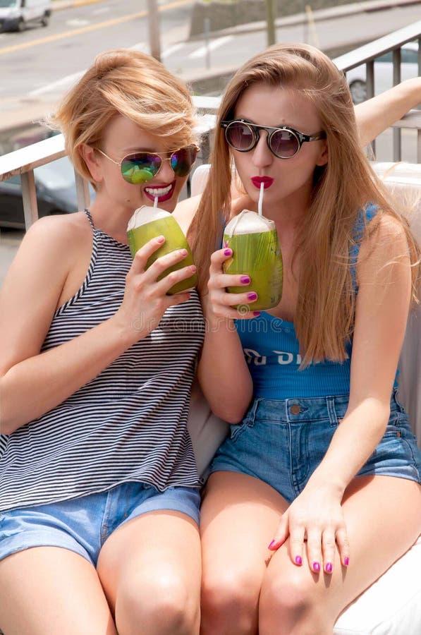 Zwei junge Frauen, die Spaß haben und Cocktail im Sommertag trinken lizenzfreies stockbild
