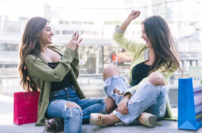 Zwei junge Frauen, die Spaß im Stadtzentrum haben lizenzfreie stockbilder