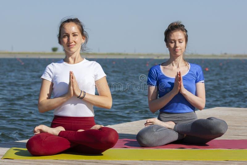 Zwei junge Frauen, die Yoga an der Natur tun Eignung, Sport, Yoga und gesundes Lebensstilkonzept - Gruppe von Personen, die an Yo stockbild