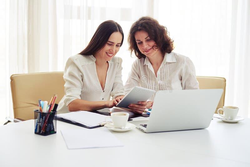 Zwei junge Frauen, die zusammen mit Geräten im Büro arbeiten stockfotos