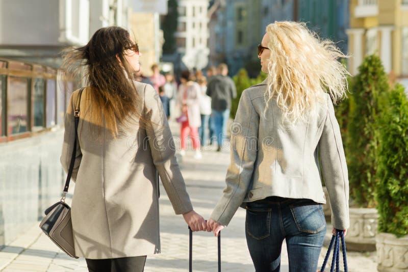 Zwei junge Frauen gehen entlang eine Stadtstraße, sonniger Herbsttag, goldene Stunde, Ansicht von der Rückseite stockfotografie