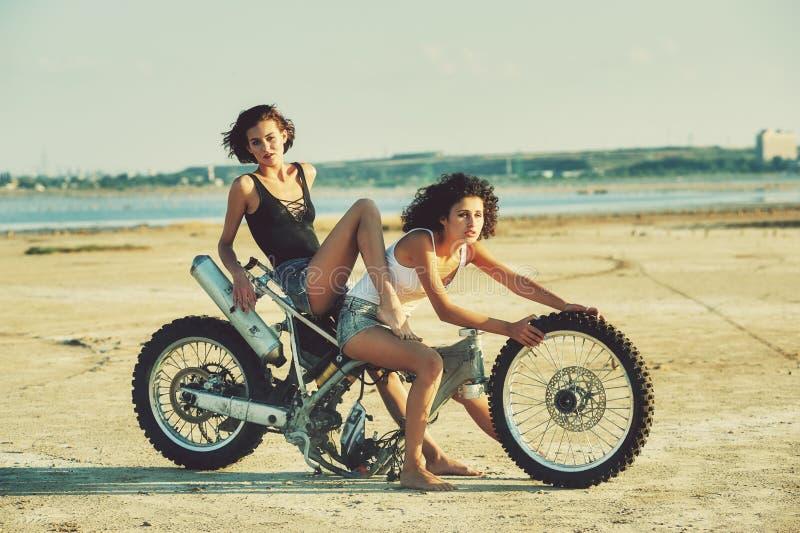 Zwei junge Frauen haben den Spaß, der auf einem auseinandergebauten Motorrad spielt lizenzfreie stockbilder