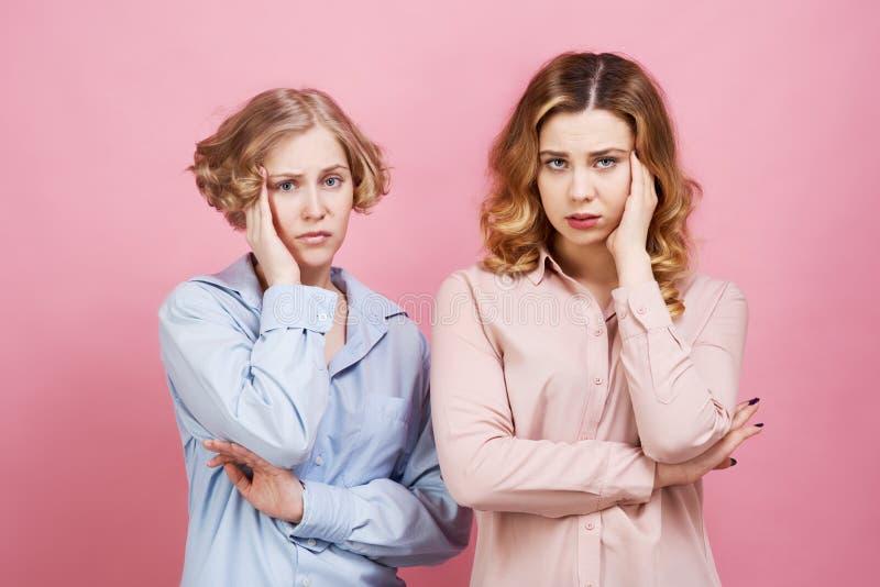 Zwei junge Frauen sind umgekippt halten und auf ihre Köpfe Kopfschmerzen und Angst verderben ihre Stimmung, sie glauben Druck, Sc stockbilder