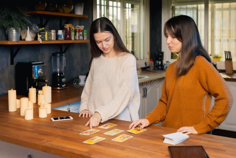 Zwei junge Frauen spielen mit Tarotkarten Ein Punkt auf einer gezogenen Karte lizenzfreies stockbild
