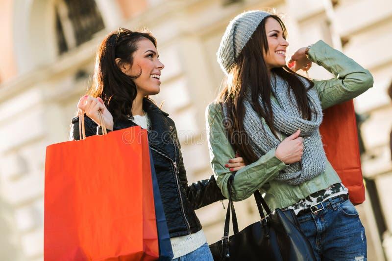 Zwei junge Frauen während shopping sprees, das Taschen und das Lächeln hält lizenzfreie stockfotos