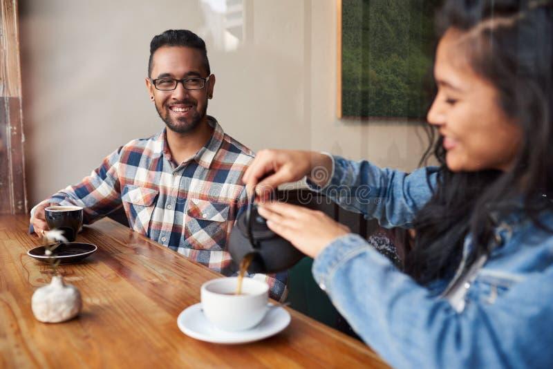Zwei junge Freunde, die zusammen über Kaffee in einem Café sprechen stockfotografie