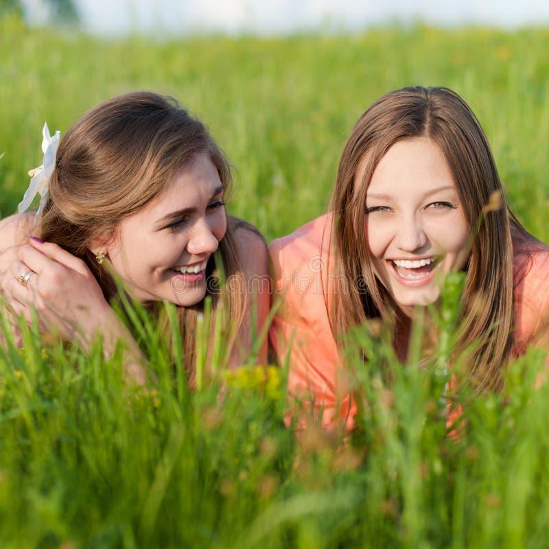 Zwei junge Freundinnen, die im grünen Gras lachen stockfotografie