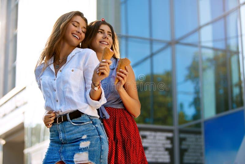 Zwei junge Freundinnen, die Spaß haben und Eiscreme essen Nette kaukasische Frauen, die draußen Eiscreme in der Stadt essen stockfotografie