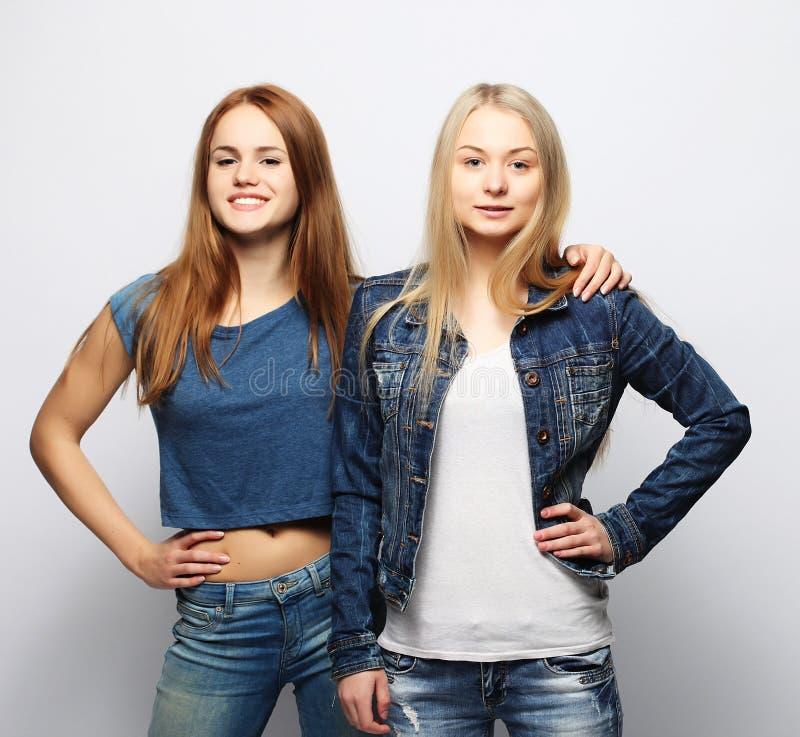 Zwei junge Freundinnen, die zusammen stehen und Spaß haben stockfoto
