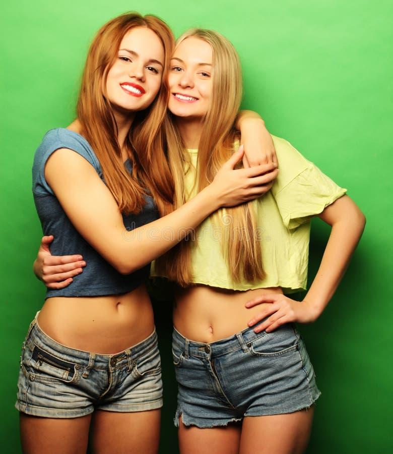 Zwei junge Freundinnen, die zusammen stehen und Spaß haben lizenzfreie stockfotos
