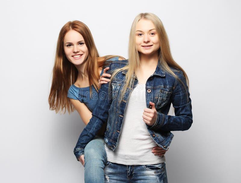 Zwei junge Freundinnen, die zusammen stehen und Spaß haben stockbilder