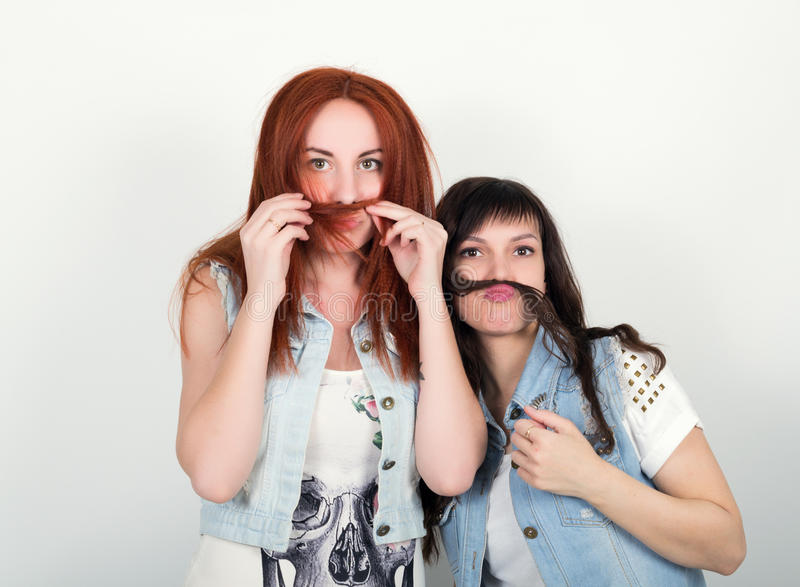 Zwei junge Freundinnen geben sich hin und verziehen Gesicht, stellen sich einen Schnurrbart aus dem Haar heraus her Jugendlicher, lizenzfreie stockfotografie