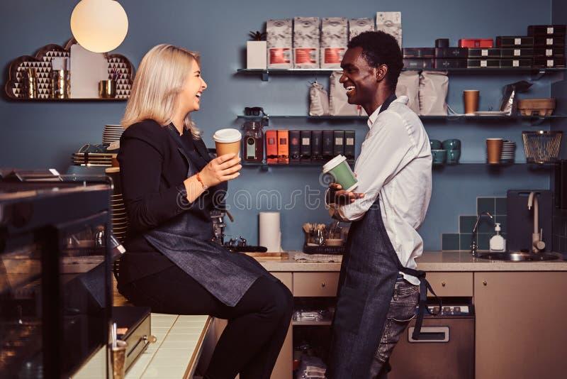 Zwei junge gemischtrassige baristas, die sich nach der Arbeit zusammen lachen und sprechen an der modischen Kaffeestube entspanne stockfotografie