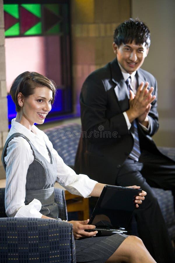 Zwei junge Geschäftsarbeitskräfte im Bürowarteraum lizenzfreies stockbild
