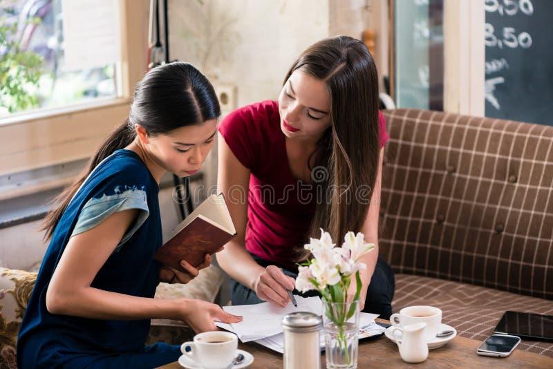 Zwei junge Geschäftsfrauen in einer Kaffeestube stockfotografie