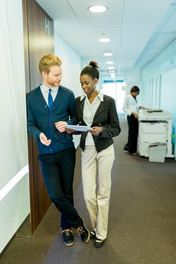 Zwei junge Geschäftsleute, die Ideen auf einem Bürokorridor besprechen lizenzfreies stockfoto