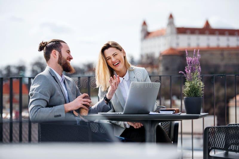 Zwei junge Geschäftsleute mit dem Laptop, der auf einer Terrasse außerhalb des Büros, arbeitend sitzt stockfoto