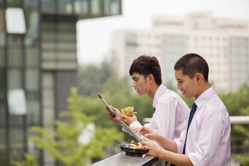 Zwei junge Geschäftsmänner, die draußen über Mittagspause arbeiten und essen stockfotografie