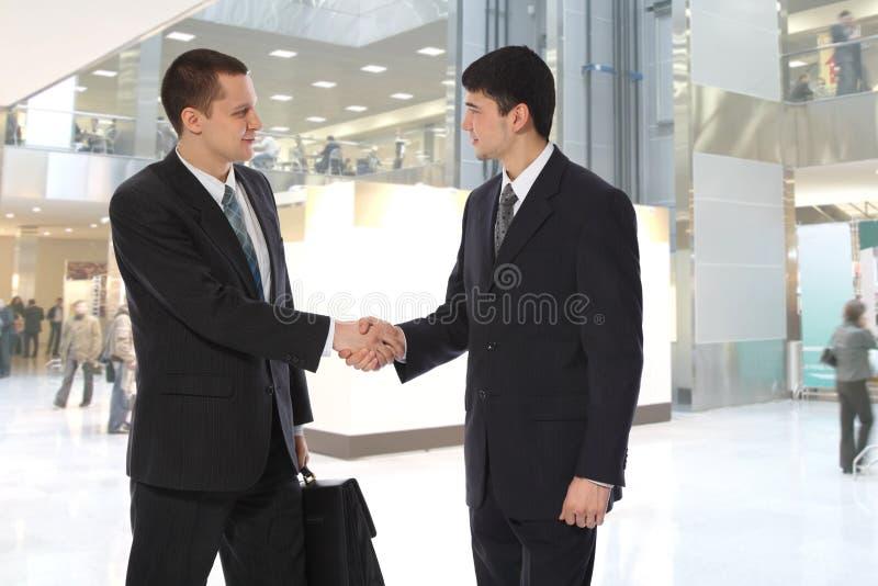 Zwei junge Geschäftsmänner grüßen lizenzfreies stockbild