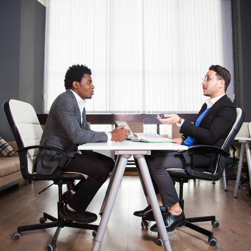 Zwei junge Geschäftsmänner, weißer Schreibtisch, Vorstellungsgespräch, Teamwork stockbild