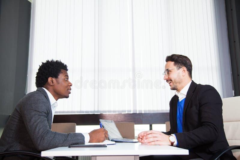 Zwei junge Geschäftsmänner, weißer Schreibtisch, Vorstellungsgespräch, Teamwork lizenzfreie stockfotografie