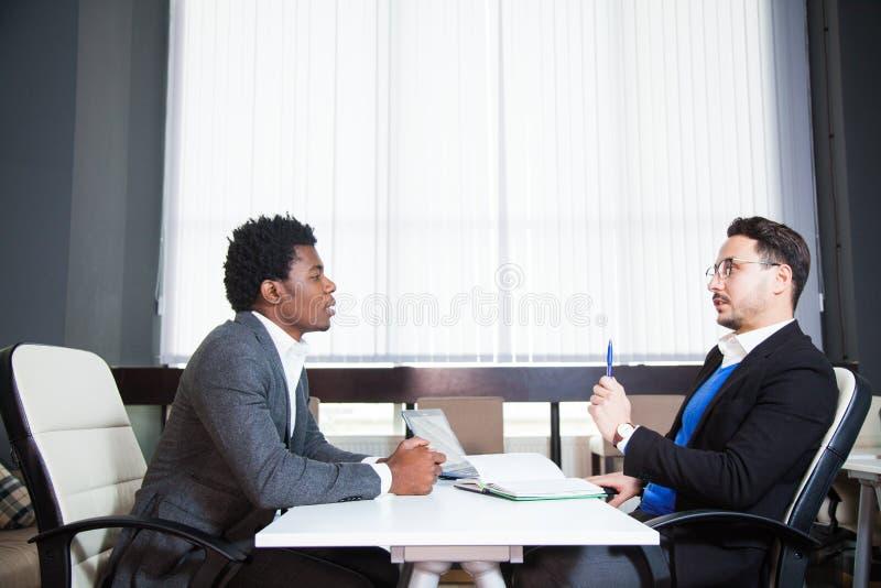 Zwei junge Geschäftsmänner, weißer Schreibtisch, Vorstellungsgespräch, Teamwork lizenzfreies stockfoto
